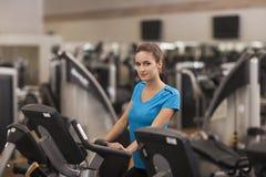 Женщина детенышей подходящая используя велосипед в фитнес-центре, cardio Портрет девушки в спортзале, концепции фитнеса образа жи Стоковая Фотография RF