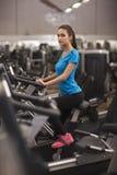 Женщина детенышей подходящая используя велосипед в фитнес-центре, cardio Портрет девушки в спортзале, концепции фитнеса образа жи Стоковые Изображения RF