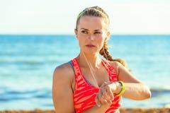 Женщина детенышей подходящая на браслете фитнеса установки берега моря Стоковое Изображение RF