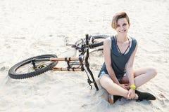 Женщина детенышей усмехаясь активная сидит на песке с велосипедом стоковые фото