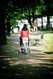 женщина детской дорожной коляски гуляя Стоковые Фото