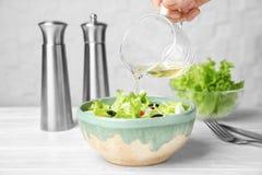 Женщина добавляя вкусный уксус яблока в салат стоковая фотография rf