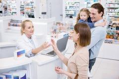 Женщина довольного женского аптекаря советуя с Стоковые Изображения RF