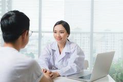 Женщина доктора и пациент мужчины обсуждают Стоковая Фотография