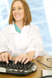 женщина доктора печатая на машинке Стоковые Изображения