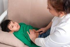 Женщина доктора рассматривает больного школьника ребенка в офисе Стоковое фото RF