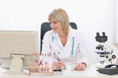 Женщина доктора среднего возраста работая на офисе Стоковое Изображение RF
