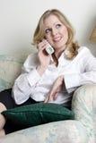 женщина домашнего телефона ослабляя говоря стоковое изображение