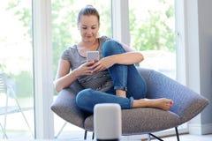 Женщина дома течь музыка от мобильного телефона к беспроводному диктору стоковые изображения rf