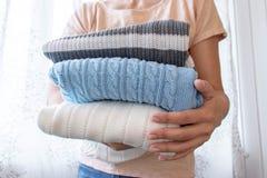 Женщина, домохозяйка держа стог одежд в поднимающем вверх рук близкое стоковые фотографии rf