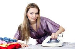 Женщина домохозяйка утюживет полотно стоковое изображение