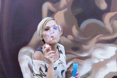 Женщина дует пузыри Стоковое Изображение