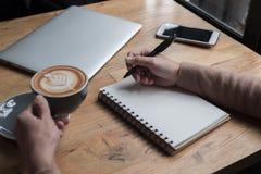 Женщина думает концепция дела на офисе она держа чашку с кофе на таблице имейте компьтер-книжку и smartphone Стоковые Фотографии RF