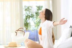 Женщина дышая в гостиничном номере в летних каникулах стоковые фото