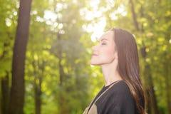 Женщина дышая свежим воздухом в зеленом лесе весной нося плащпалату шерстей стоковые фотографии rf