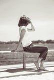 Женщина девушки в джинсах сидя около воды Стоковая Фотография RF
