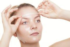 Женщина девушки в лицевом слезает маску прикладывать политуру кожи внимательности прозрачную Стоковые Изображения