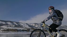 Женщина едет велосипед на льде Девушка одета в серебристой вниз куртке, задействуя рюкзаке и шлеме Лед  акции видеоматериалы