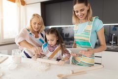 Женщина, ее дочь и бабушка подготавливают домодельное печенье Женщина проверяет рецепт на таблетке Стоковые Фото