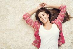 Женщина лежа вниз на ковре, счастливом молодом взрослом портрете девушки стоковое фото rf