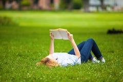 Женщина лежа в траве и читая книгу Стоковые Изображения