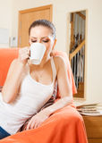 Женщина лежа на кресле и выпивая кофе Стоковые Изображения