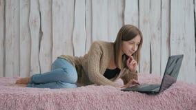 Женщина лежа на кровати и используя компьтер-книжку Стоковая Фотография