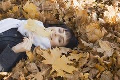 Женщина лежа на осенних листьях Стоковое Изображение RF