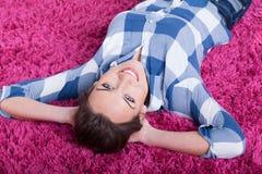 Женщина лежа на розовом ковре стоковые изображения