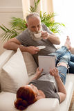 Женщина лежа на софе с кофе цифровой таблетки и бородатого человека выпивая дома Стоковое Изображение