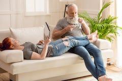 Женщина лежа на софе с кофе цифровой таблетки и бородатого человека выпивая дома Стоковое фото RF
