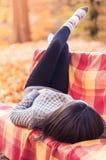Женщина лежа на стенде против предпосылки парка Стоковые Изображения RF