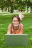 Женщина лежа на траве и используя компьтер-книжку Стоковые Изображения