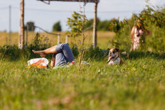 Женщина лежа на траве с собакой Стоковое Изображение