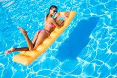 Женщина лежа на тюфяке воздуха в бассейне Стоковая Фотография RF
