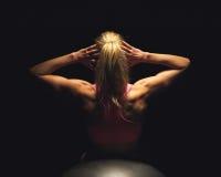 Женщина лежа на шарике пригодности и делая сидит поднимает стоковое фото