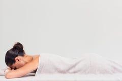 Женщина лежа на lounger массажа стоковые фото