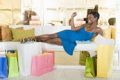 Женщина лежит с хозяйственными сумками в зоне отдыха магазина Стоковое фото RF