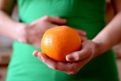Женщина держа апельсин Стоковое Фото