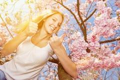 Женщина держа большие пальцы руки вверх на цветении вишневого дерева Стоковые Изображения RF