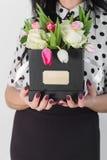 Женщина держа букет роз и тюльпанов в коробке Стоковая Фотография
