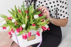 Женщина держа букет роз и тюльпанов в коробке Стоковые Фотографии RF