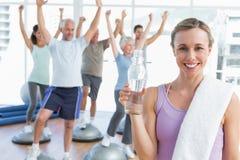 Женщина держа бутылку при люди протягивая руки на студии фитнеса Стоковое Изображение RF