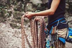 Женщина держа взбираясь веревочку около утеса Стоковое Изображение RF