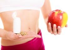 Женщина держа витамины и яблоко здоровье внимательности рукояток изолировало запаздывания Стоковые Фото