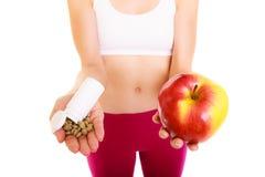Женщина держа витамины и яблоко здоровье внимательности рукояток изолировало запаздывания Стоковая Фотография