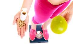 Женщина держа витамины и яблоко здоровье внимательности рукояток изолировало запаздывания Стоковое фото RF