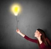 Женщина держа воздушный шар лампочки Стоковая Фотография RF