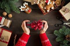 Женщина держа в подарке на рождество рук с красной лентой Концепция Xmas Стоковые Фото