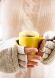 Женщина держа горячий испаряясь конец кофейной чашки вверх по фото Стоковые Фотографии RF